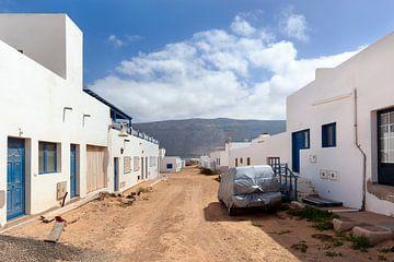 Leere Straße mit Sand und weißen Häusern und ein in Plastik eingewickeltes Auto gegen das Wetter in  von Peter de Kievith Fotografie