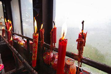 Brennende rote Kerzen im chinesischen buddhistischen Tempel