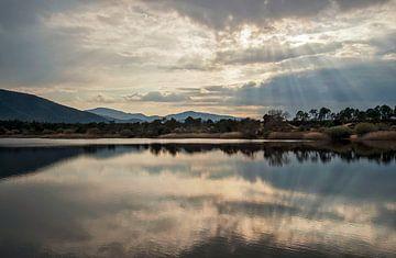 Zonnestralen boven een meer in de bergen van