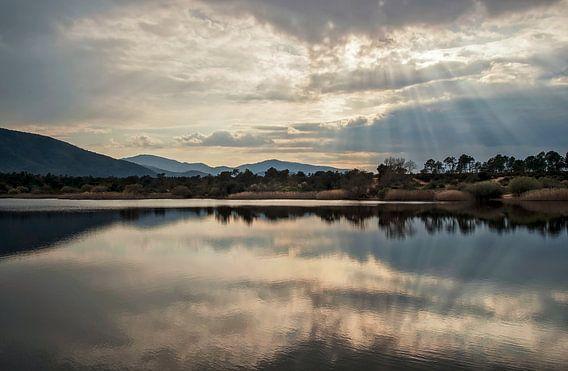 Zonnestralen boven een meer in de bergen