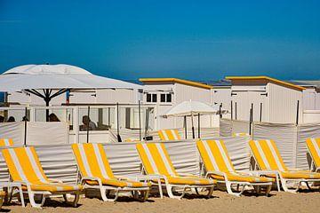 Ligstoelen bij strandhuisjes van
