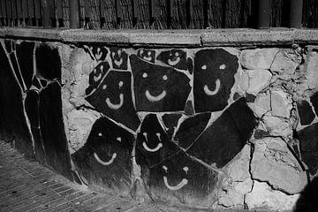 lachende gezichten gegrafiteerd op de stenen muur van Thomas Kaltofen