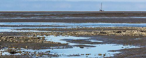 Waddenzee bij eb met oesterbanken en drooggevallen zeilschip van