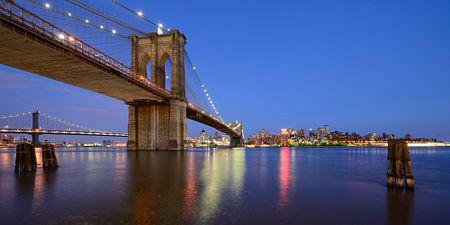 Brooklyn Bridge in New York over de East River in de avond, panorama