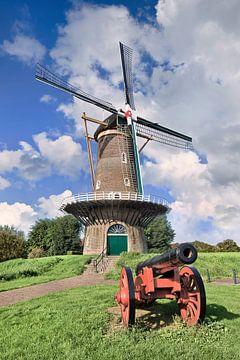 Traditionele Nederlandse windmolen op met een oude rode canon vooraan van Tony Vingerhoets