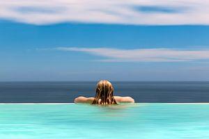 Meisje kijkt naar de zee vanuit infinity pool