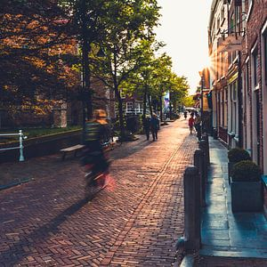 Cyclist going through Delft with sunset