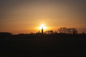 Coucher de soleil avec une silhouette de l'église Sint Baafs à Aardenburg sur StephanvdLinde