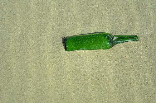 Bierflesje van het merk Grolsch liggend in het zand.