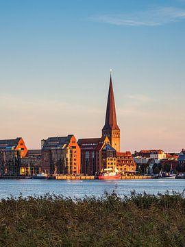 Uitzicht over de Warnow naar de Hanzestad Rostock in de avond van Rico Ködder