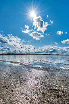 Wolkenlucht boven een spiegelend wateroppervlak van de Waddenzee van Harrie Muis