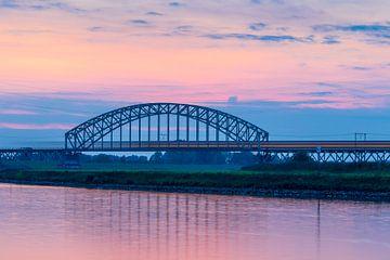 Zug auf Eisenbahnbrücke nach Sonnenuntergang von Thijs Vermeer