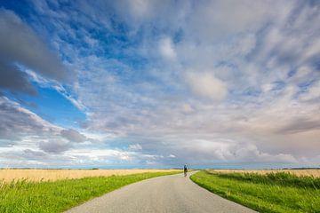 Wielrenner op landweg in Lauwersmeergebied van Jurjen Veerman
