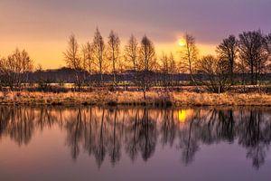Dageraad met blauwe lucht en bosrand uiting in een lake_1