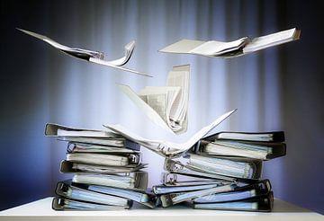 fliegende Ringbücher mit Akten und Dokumenten landen auf Stapeln auf einem Büroschreibtisch, Konzept von Maren Winter