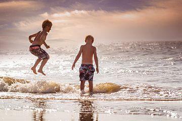 kinderen springen en spelen bij zonsondergang van Kim Groenendal