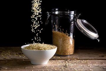 rijstkorrels die in een witte kom vallen naast een glazen pot met rijst op een rustieke houten tafel van Maren Winter