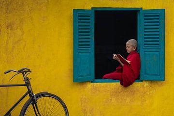 Een boek lezen in het raam kozijn van Anges van der Logt