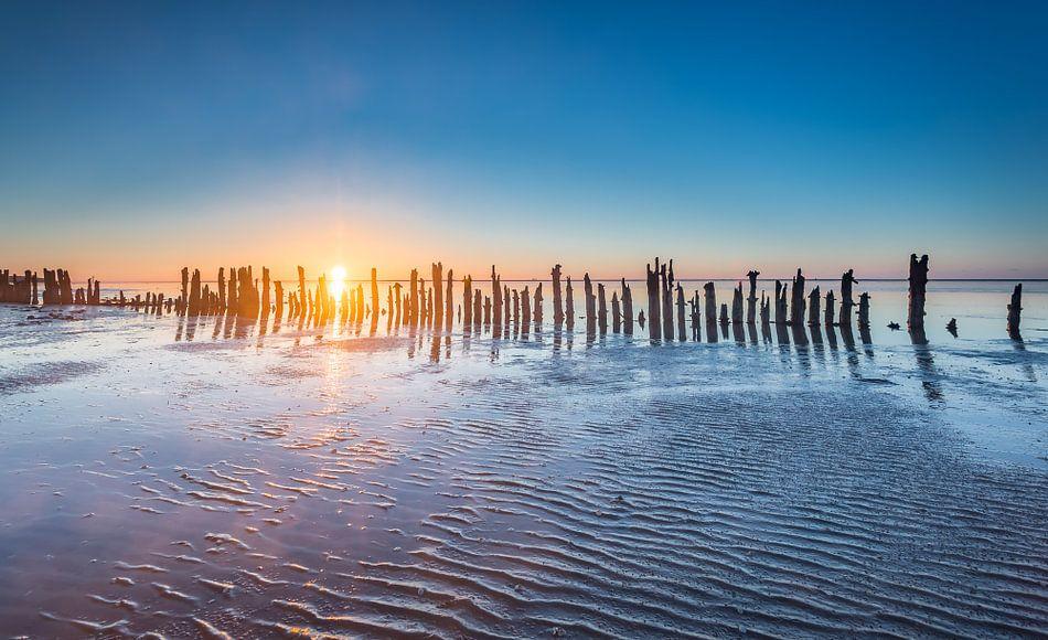 Paaltjes aan de Waddenzee tijdens zonsondergang