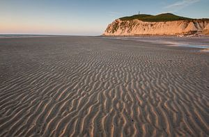 Ribbels in het zand met krijtrotsen op de achtergrond bij ondergaande zon