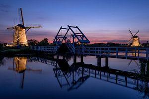 Verlichte molens en een ophaalbrug bij zonsondergang