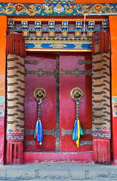 Rote Tür mit Gebetsfahnen in einem tibetischen Kloster von Rietje Bulthuis