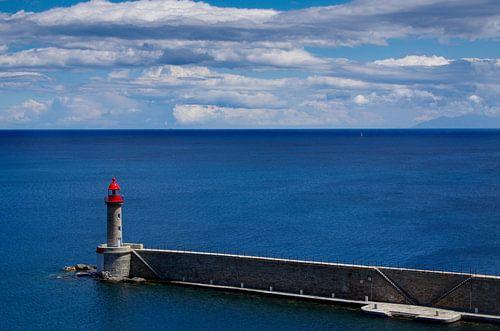 Leuchtturm vor ruhigem tiefblauem Meer.