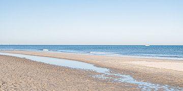 Het Scheveningse strand en zee met een zeilboot. van MICHEL WETTSTEIN
