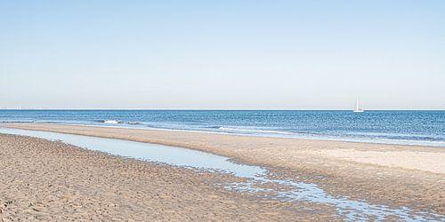 Het Scheveningse strand en zee met een zeilboot.