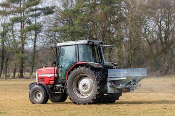Rode tractor op een weiland met een kalkspreider in het vroege voorjaar in Nederland van Tonko Oosterink
