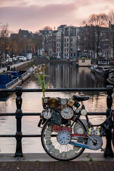 Fiets met klokken op de Amsterdamse grachten van Andrea de Jong