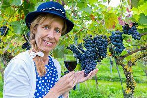 Vrouw in wijngaard toont blauwe druiven met wijn