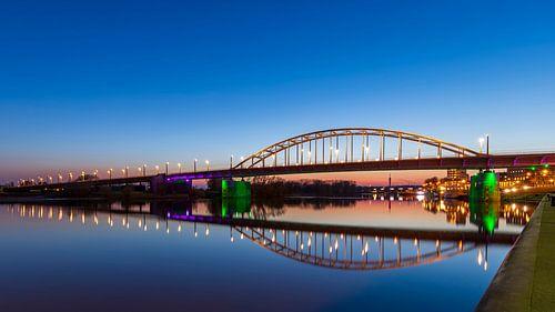 De Arnhemse John Frostbrug 's avonds boven een vlakke Rijn van
