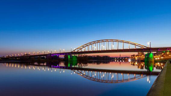 De Arnhemse John Frostbrug 's avonds boven een vlakke Rijn