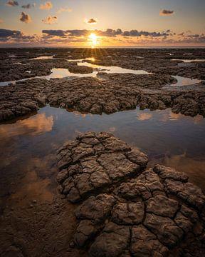 Modder bij Waddenzee tijdens zonsondergang
