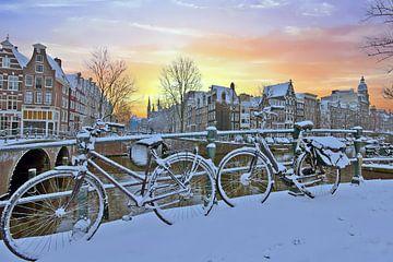 Winter in besneeuwd Amsterdam bij zonsondergang van nilaya van vliet