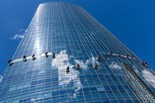 Glazenwassers hangen aan touw terwijl ze de ramen van een glazen wolkenkrabber in Buenos Aires schoo van