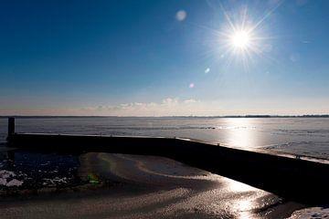 Zon over een bevroren meer in Nederland. van