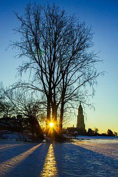 Zonsopkomst op een bevroren meer met een klein kerkje. van Sara de Leede