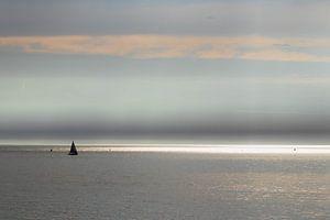 Zonnestralen en zeiljacht op zee