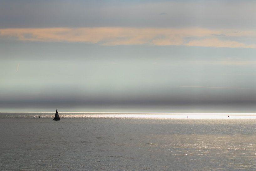 Zonnestralen en zeiljacht op zee van Anne Zwagers