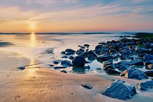 Golfbrekers met strand bij een zonsondergang