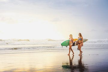 Surfers tijdens zonsondergang. van Andy Troy