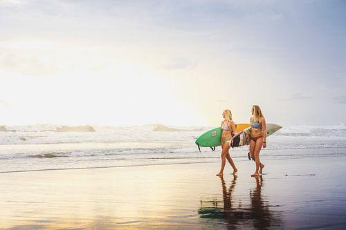 Surfers tijdens zonsondergang.