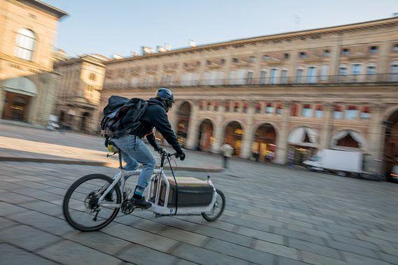 Bezorger op de fiets op Piazzo Maggiore met grote haast
