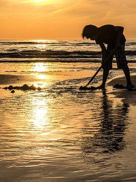 Jongen aan oranje strand van