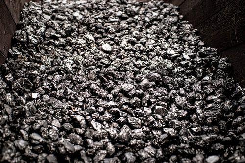 Opgestapelde zwart glimmende kolen in een houten box voor oude industrie
