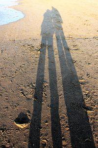 Lange schaduw van een koppel op het strand