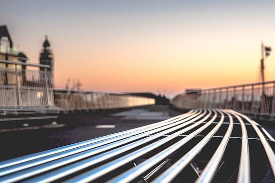 Moderne metalen design bank langs boulevard tijdens zonsondergang