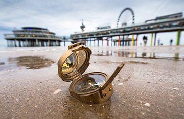 Een zeekompass op het strand in Scheveningen. Op de achtergrond is de Pier zichtbaar. van Claudio Duarte